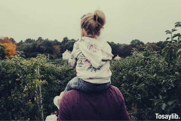 daughter riding on his father s shoulder