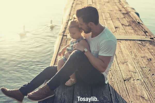 father and daughter sitting on brown deck