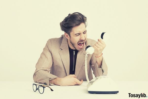 man holding telephone shouting