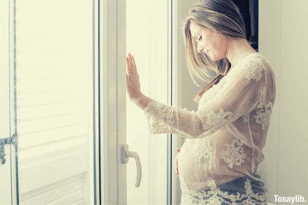 01 photo of pregnant woman standing in front of door