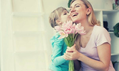 girl-kissing-godmother-cheek-pink-flowers