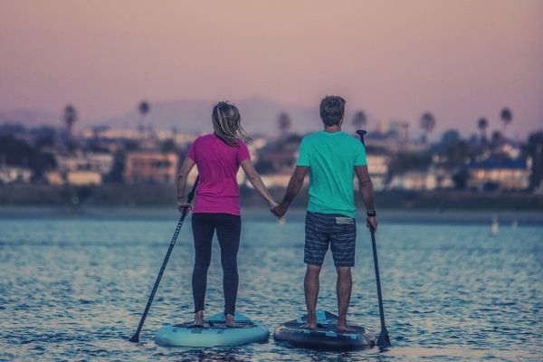 man-and-woman-standing-on-a-paddle