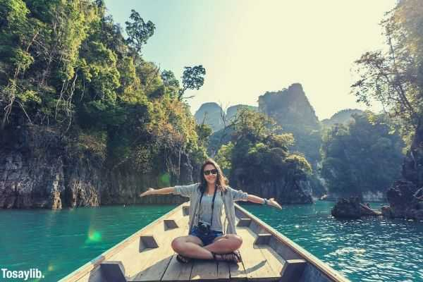 photo of a woman sitting on a boat raising her hand