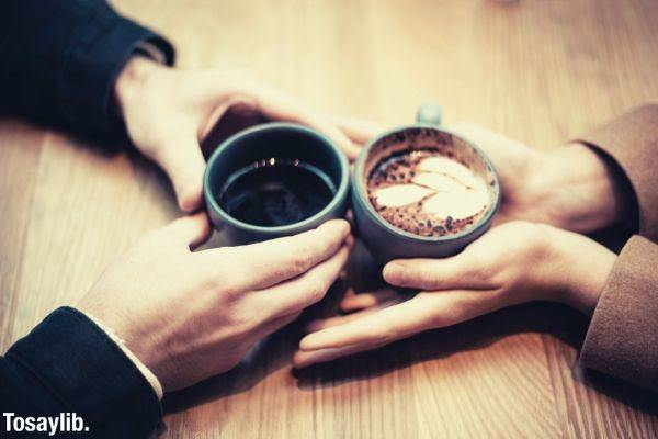 two person holding ceramic cup with coffee