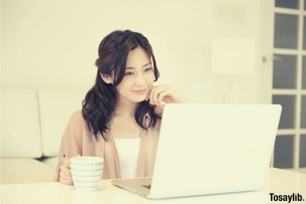 woman looking laptop drinking coffee
