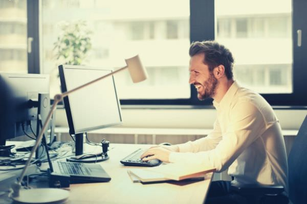 man-in-white-dress-shirt-sitting-office-on-black-rolling-chair-while-facing-black-computer-set-and-smiling
