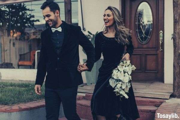 photo of couple holding hands white bouquet black clothes