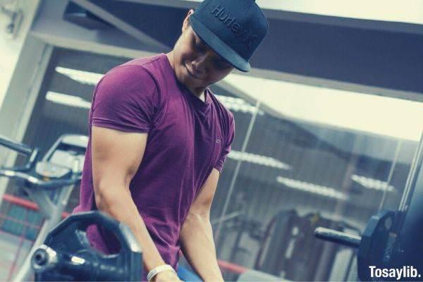 man exercising dumbell maroon tshirt
