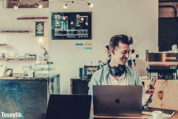 man using laptop phone headset