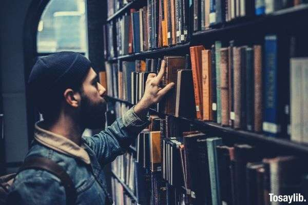 man looking for books library