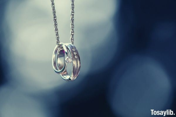 silver colored ring pendant hanging on a chain