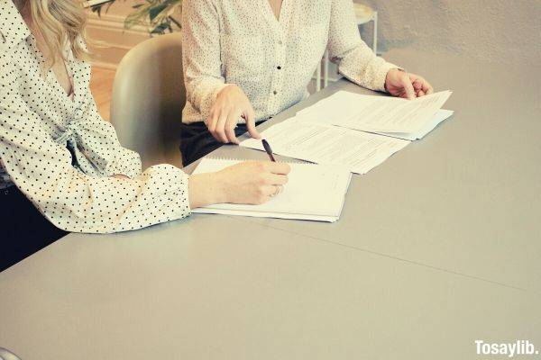 woman signing on white paper