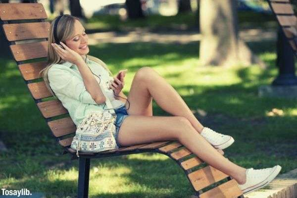 woman sititng on a bench listening to music