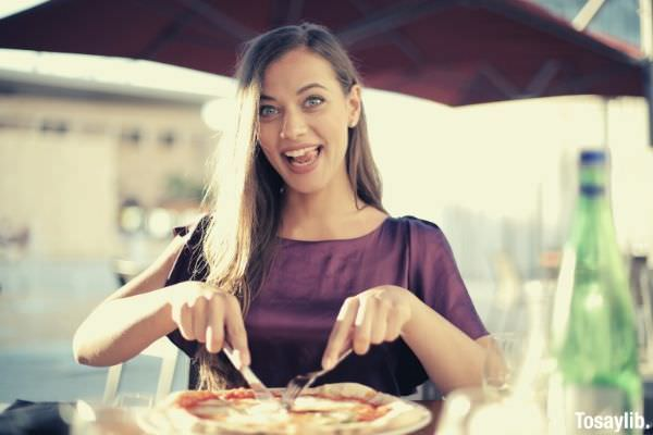 photo of woman purple top slicing pizza