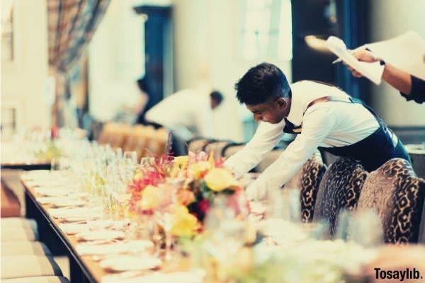man organizing table plates glasses flowers