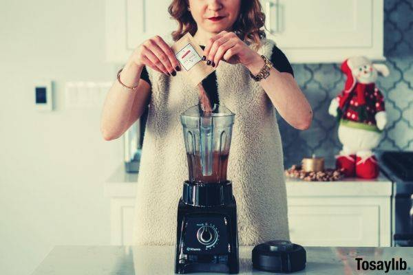 woman putting powdered tonic bar drink in the black blender
