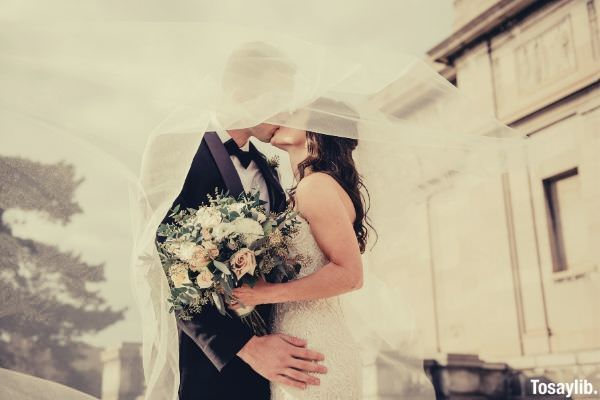 man and woman newly wed kissing bouquet of flowers
