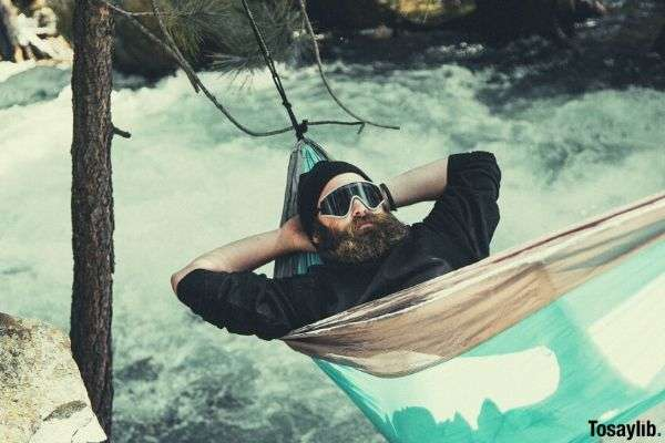 man wearing shades reclining on blue and brown hammock