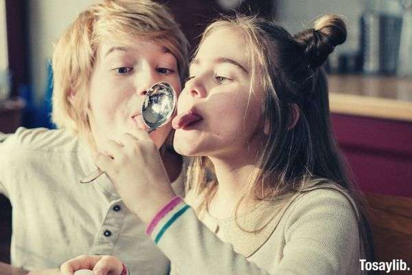 kids making funny faces on stainless spoon