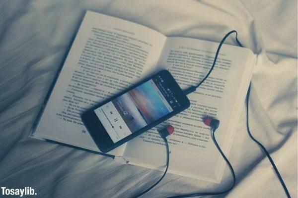 black smart phone on white book black earphones