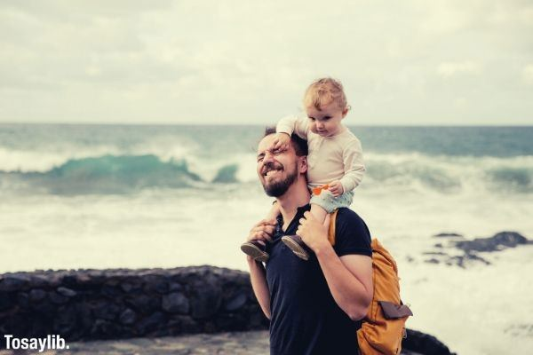 man in black shirt carrying little kid on his shoulder sea