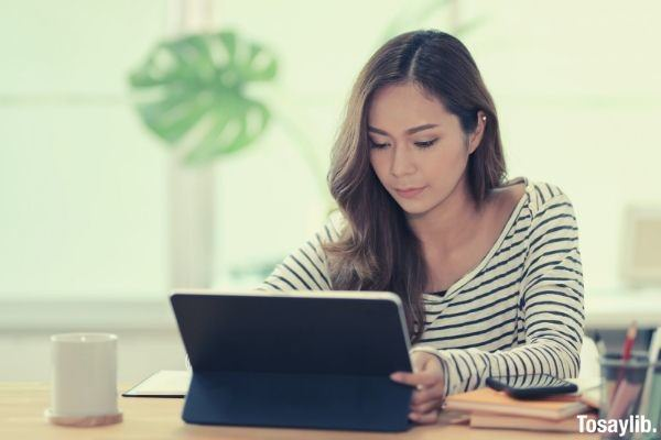 woman in black and white striped dress shirt using black tablet computer