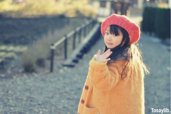 girl with yellow knitted sweater and beanie waving goodbye