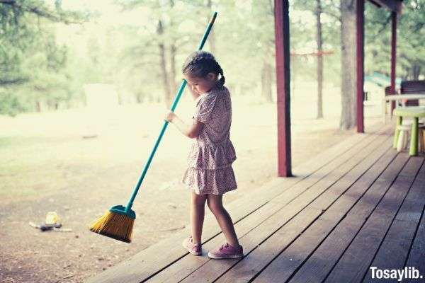 girl sweeping at the cabin