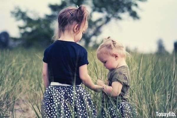 two little girls standing on grass field