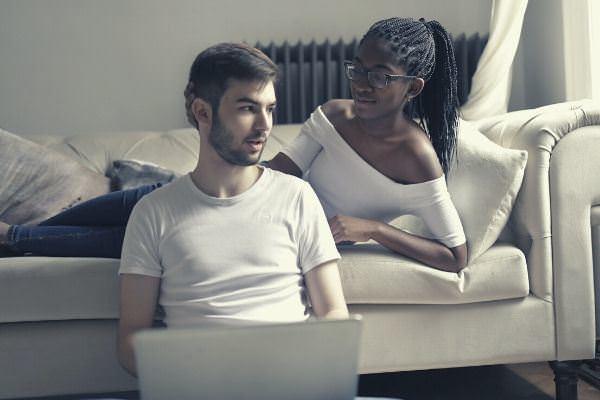 02 couple wearing white tops girl lying sofa man sitting holding laptop