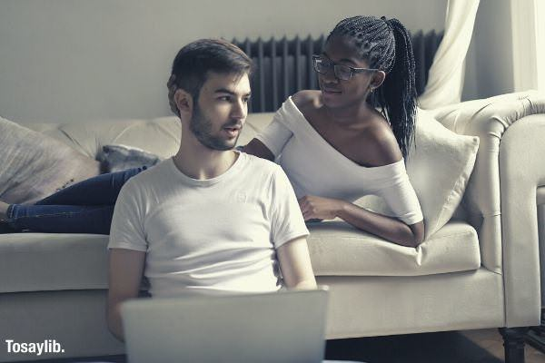 02 feature couple wearing white tops girl lying sofa man sitting holding laptop