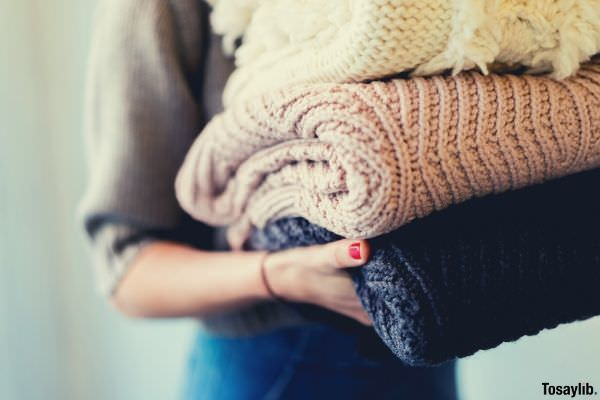 04 person holding hand knitted clothes