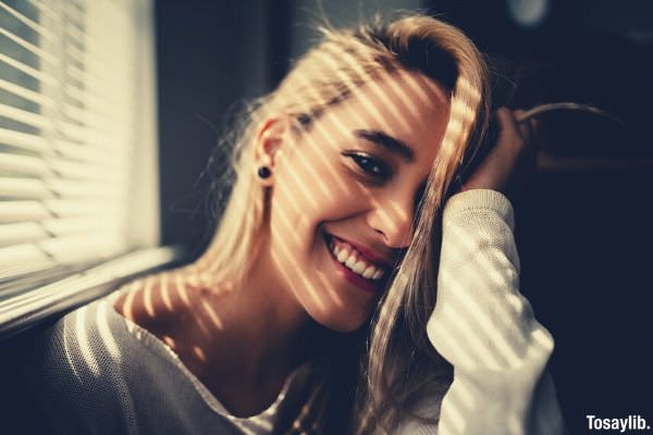 photo of a woman smiling holding her blonde hair
