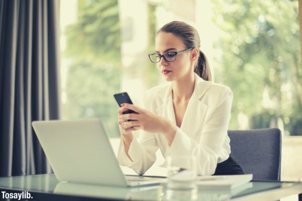 serious businesswoman wearing glasses using smartphone in workplace