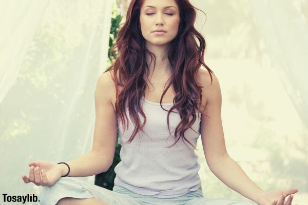 woman doing yoga pose sitting on the wooden platform
