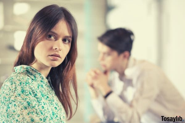 woman in green blouse looking away from the man sitting
