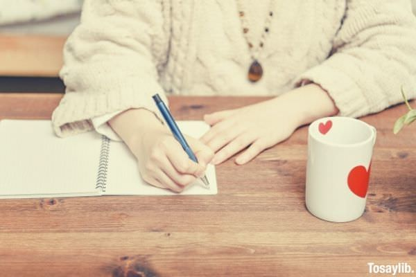 woman taking notes in notebook mug hearts