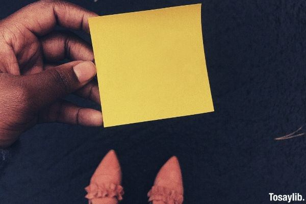 person holding sticky note paper shoes