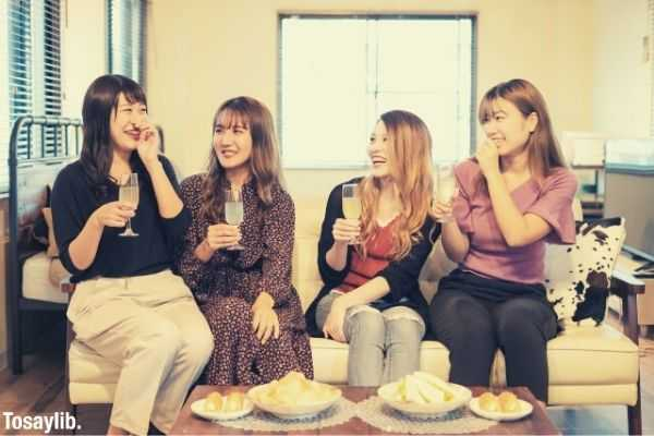 photo of women sitting on the chair while having conversation and foods
