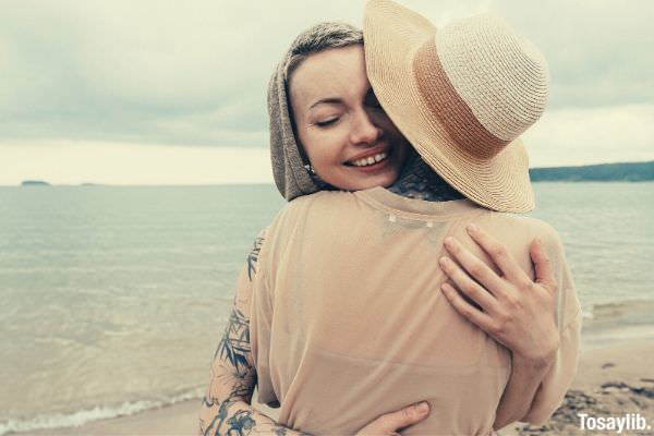 two women hugging each other wearing beige clothes