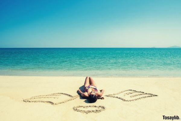girl with angel wings on the beach written on the sand