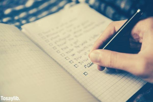 person writing bucket list on notebook with grids
