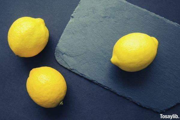 three yellow citrus lemon on top of black table