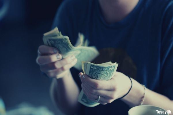 woman wearing blue shirt counting money