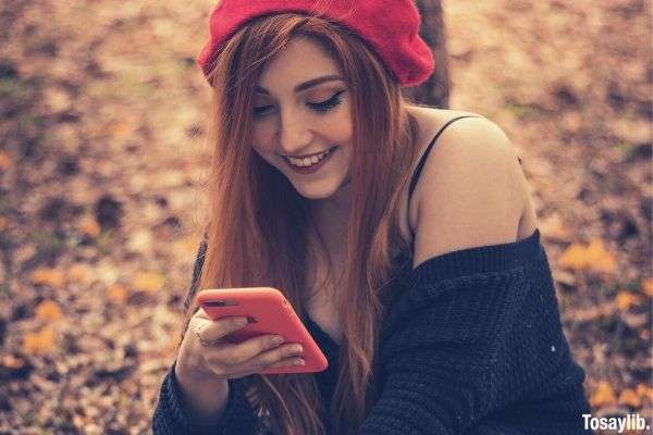 selective focus photography of sitting and smiling woman using smartphone wearing red beanie