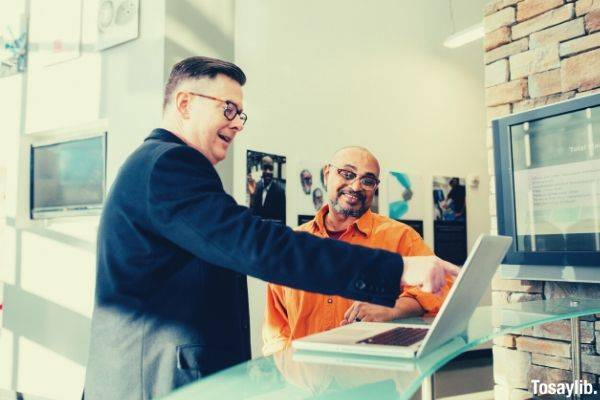 formal man pointing something laptop with another man in orange