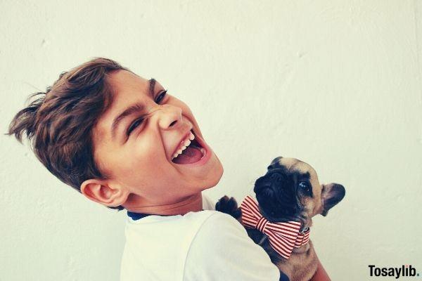 boy holding dog photo while smiling