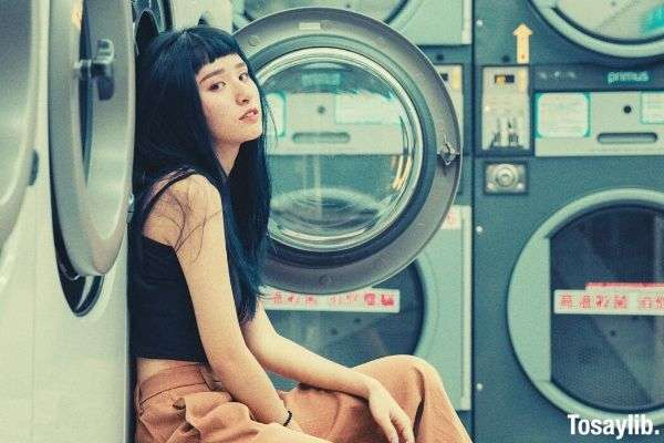 girl sitting on front load washing machine