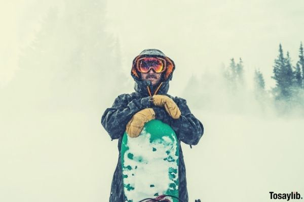 snow storm man wearing coat glasses and with snowboard