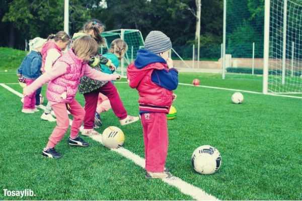 kids playing soccer ball net field